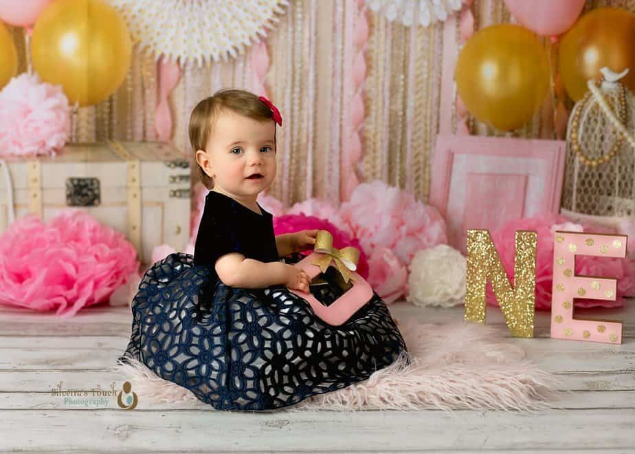 Cake smash photography of baby girl in blue dress smiling with Babydream backdrop decoration